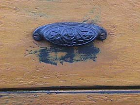 drawer handle painted yellow, with wear